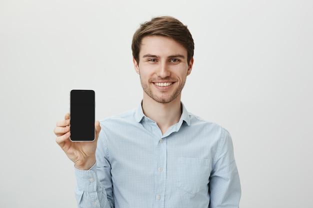 Przystojny uśmiechnięty biznesmen promuje aplikację mobilną, pokazując wyświetlacz smartfona