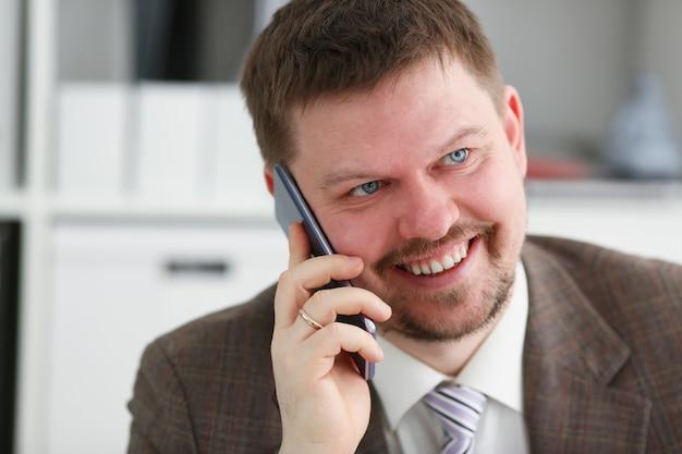 Przystojny uśmiechnięty biznesmen rozmowy telefon komórkowy