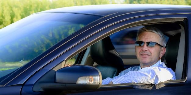 Przystojny uśmiechnięty biznesmen siedzi w samochodzie