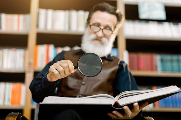 Przystojny uśmiechnięty brodaty mężczyzna, bibliotekarz lub profesor, w bibliotece, siedzący na tle regałów, trzymając szkło powiększające i czytanie książki. skoncentruj się na szkle i książce