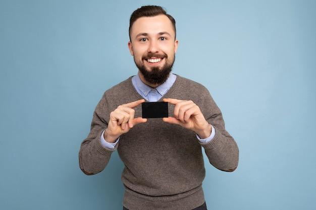 Przystojny uśmiechnięty brodaty mężczyzna brunetka ubrana w szary sweter i niebieską koszulę na białym tle na tle ściany trzyma kartę kredytową patrząc na kamery.
