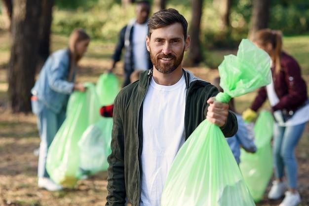 Przystojny, uśmiechnięty brodaty mężczyzna trzyma worek na śmieci na tle swoich przyjaciół działaczy zbierających śmieci w parku