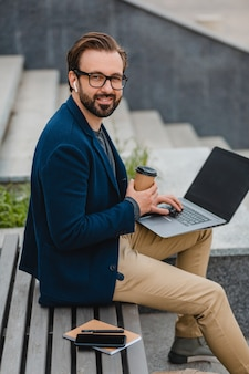 Przystojny uśmiechnięty brodaty mężczyzna w okularach pracujący na laptopie