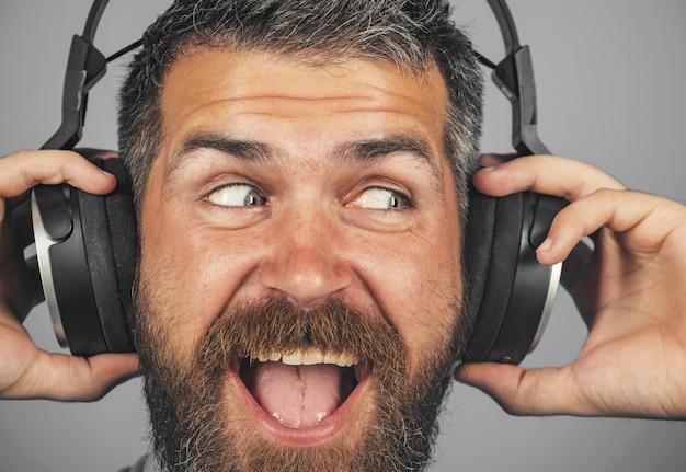 Przystojny uśmiechnięty brodaty mężczyzna ze słuchawkami. emocjonalny mężczyzna z słuchawkową muzyką słuchania.