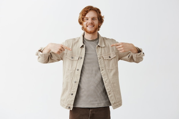 Przystojny uśmiechnięty brodaty rudy facet pozowanie na białej ścianie