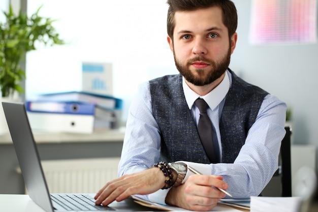 Przystojny uśmiechnięty brodaty urzędnika mężczyzna przy biurowym miejscem pracy
