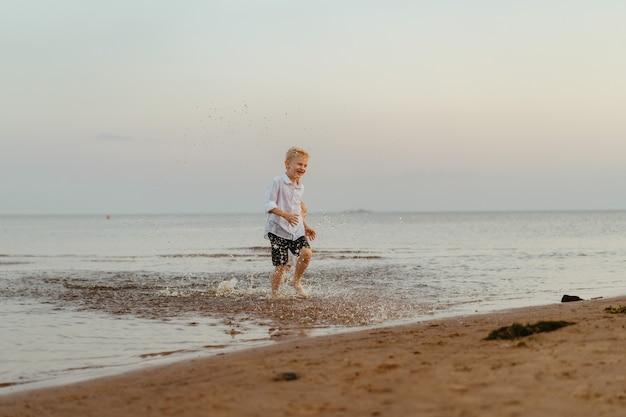 Przystojny uśmiechnięty chłopiec kaukaski ubrany w białą koszulę i szorty, biegnący od morza