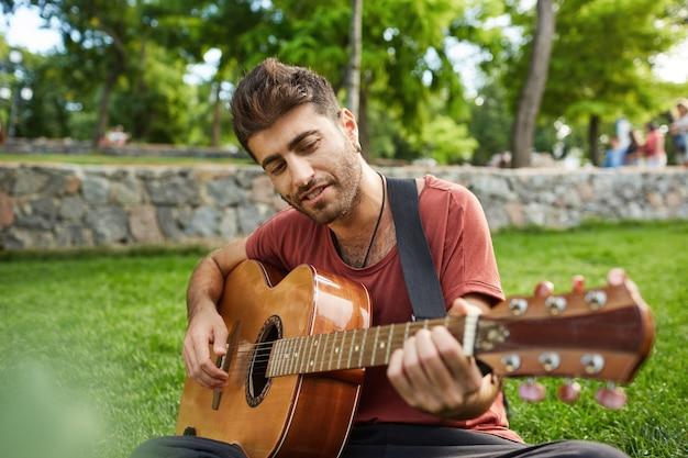 Przystojny uśmiechnięty facet gra na gitarze w parku, siedząc na trawie, mając beztroski weekend