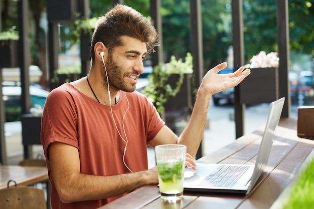 Przystojny uśmiechnięty facet rozmawia ze współpracownikami, siedząc w kawiarni na świeżym powietrzu za pomocą aplikacji do rozmów wideo w laptopie i słuchawek