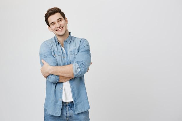 Przystojny uśmiechnięty facet stojący z rękami skrzyżowanymi