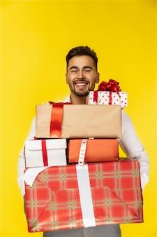 Przystojny uśmiechnięty facet trzyma prezentów pudełka
