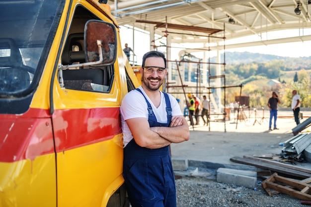 Przystojny uśmiechnięty kaukaski nieogolony pracownik w kombinezonie, opierając się na ciężarówce i trzymając skrzyżowane ramiona. zwykły dzień w rafinerii.