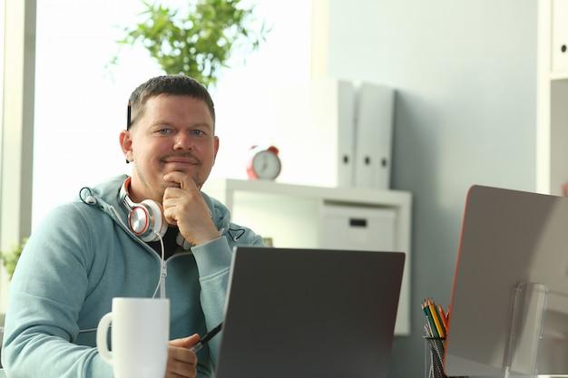 Przystojny uśmiechnięty męski uczeń używa online