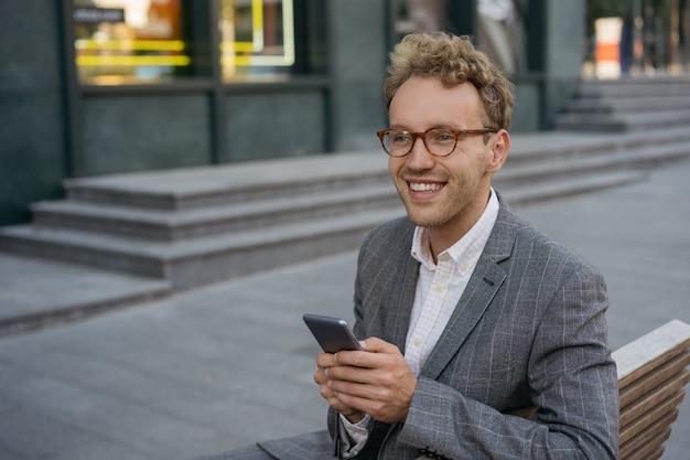 Przystojny uśmiechnięty mężczyzna noszący okulary za pomocą telefonu komórkowego robiący zakupy online, patrząc na miejsce na kopię