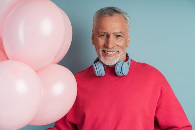 Przystojny, uśmiechnięty mężczyzna o siwych włosach nosi słuchawki, trzymając balony.