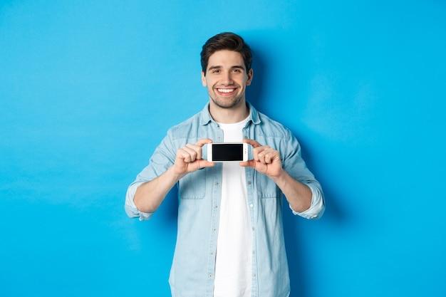 Przystojny uśmiechnięty mężczyzna pokazując ekran smartfona, stojąc na niebieskim tle na miejsce.