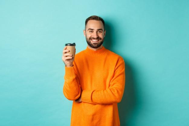 Przystojny uśmiechnięty mężczyzna robi sobie przerwę, pije kawę na wynos, stojąc na niebieskim tle.