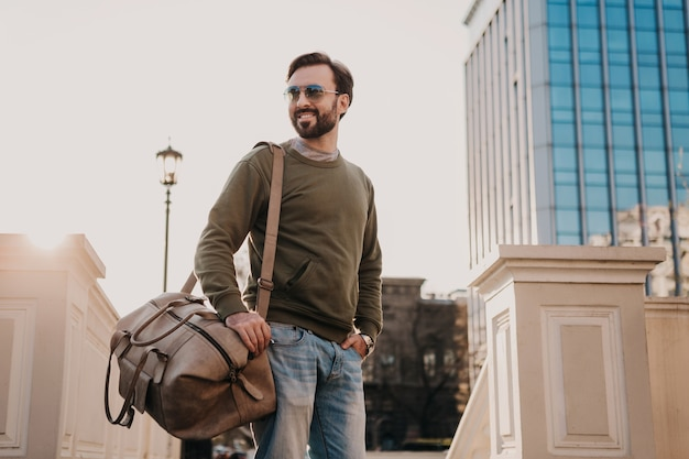 Przystojny uśmiechnięty mężczyzna stylowy hipster spaceru ulicą miasta ze skórzaną torbą na sobie bluzę i okulary przeciwsłoneczne, trend w stylu miejskim, słoneczny dzień