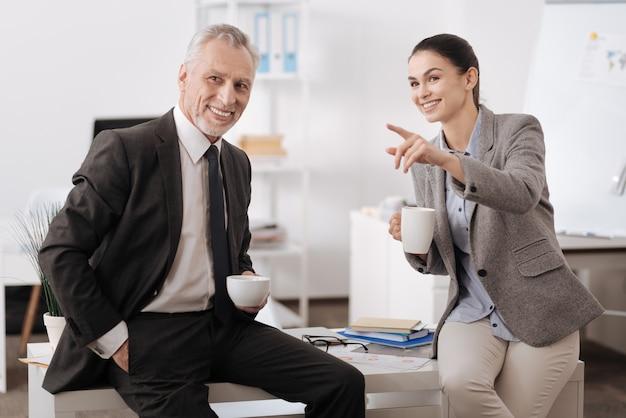 Przystojny uśmiechnięty mężczyzna trzymając kubek z kawą w lewej ręce, patrząc na boki, jednocześnie wkładając prawą rękę do kieszeni