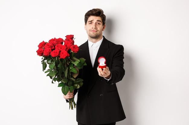 Przystojny uśmiechnięty mężczyzna w czarnym garniturze, trzymając róże i pierścionek zaręczynowy