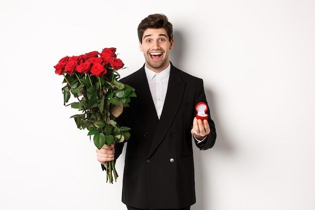 Przystojny uśmiechnięty mężczyzna w czarnym garniturze, trzymający róże i pierścionek zaręczynowy, składający propozycję małżeństwa, stojący na białym tle