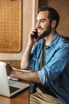Przystojny uśmiechnięty mężczyzna w dżinsowej koszuli rozmawia przez telefon komórkowy z laptopem i schowkiem podczas pracy w kawiarni w pomieszczeniu