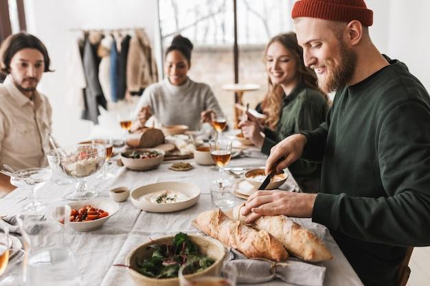 Przystojny uśmiechnięty mężczyzna w kapeluszu z brodą siedzi przy stole radośnie krojenia bagietek