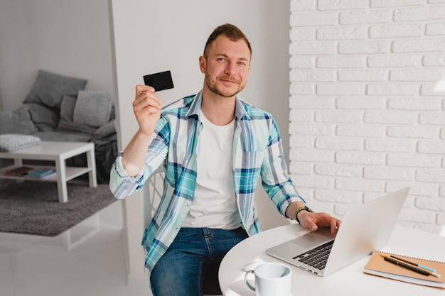 Przystojny uśmiechnięty mężczyzna w koszuli siedzi w kuchni w domu przy stole pracuje online na laptopie z domu freelancer posiadający kartę kredytową, izolacja społeczna