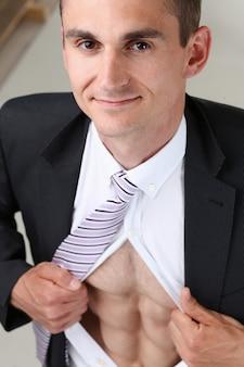 Przystojny uśmiechnięty mężczyzna w krawacie rozdziera ubrania z tułowia pokazuje abs.