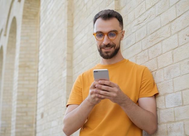 Przystojny, uśmiechnięty mężczyzna za pomocą komunikacji przez telefon komórkowy online, oglądając wideo na ulicy