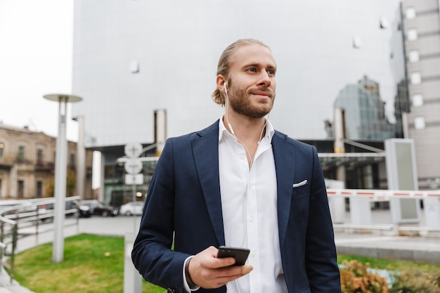 Przystojny uśmiechnięty młody brodaty biznesmen stojący na zewnątrz na ulicy, słuchający muzyki przez słuchawki, trzymający telefon komórkowy