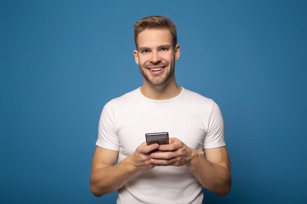 Przystojny uśmiechnięty młody człowiek używa smartphone odizolowywającego na błękicie