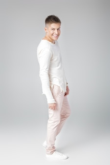 Przystojny uśmiechnięty młody człowiek w biały sweter i spodnie