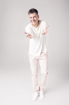 Przystojny uśmiechnięty młody człowiek w białym swetrze wyciąga rękę do przodu