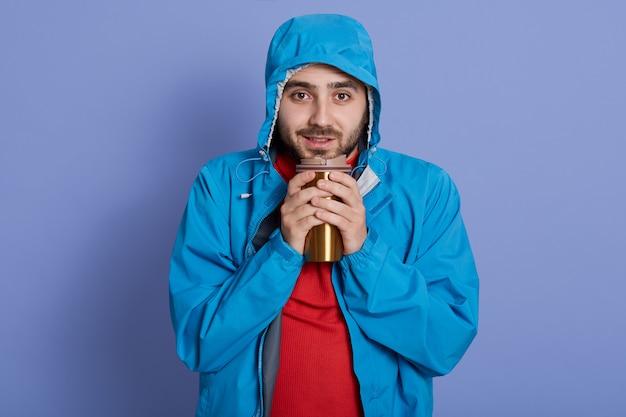 Przystojny uśmiechnięty młody człowiek z kubkiem termicznym w rękach, utrzymując ciepło, pijąc gorący napój, patrzy na kamerę, ubrany w niebieską kurtkę
