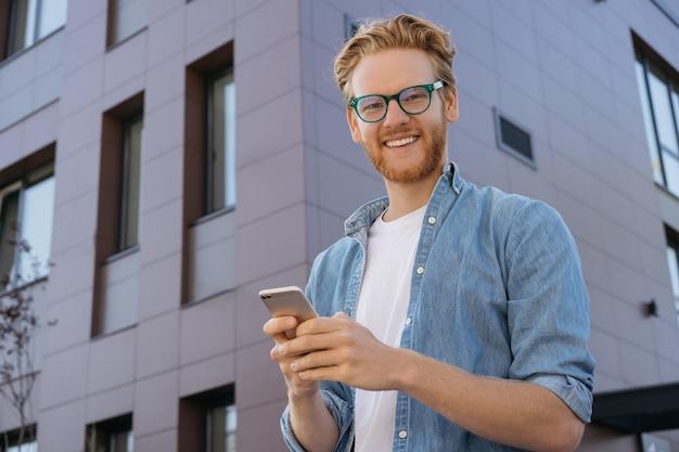 Przystojny uśmiechnięty rudowłosy mężczyzna za pomocą aplikacji mobilnej do zakupów online