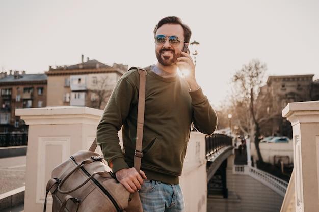 Przystojny uśmiechnięty stylowy hipster mężczyzna spacerujący ulicą miasta ze skórą rozmawiający przez telefon na torbie podróżnej w bluzie dresowej i okularach przeciwsłonecznych, trend w stylu miejskim, słoneczny dzień, podróżowanie
