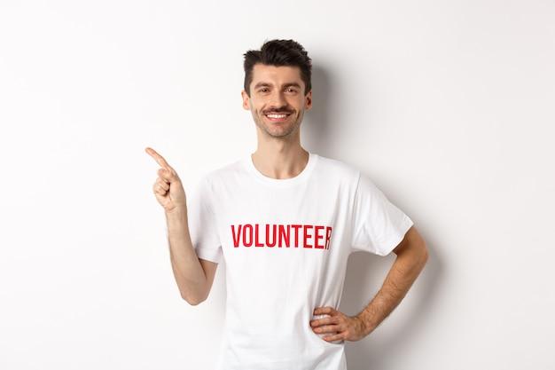 Przystojny uśmiechnięty wolontariusz w koszulce wskazując palcem w lewo, pokazując ogłoszenie, stojąc na białym.
