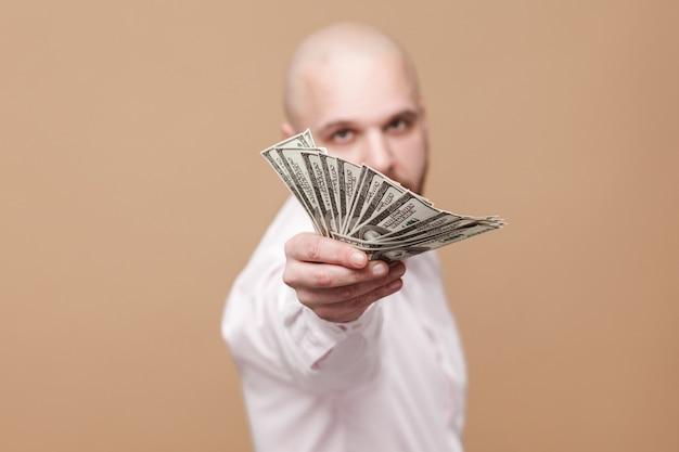 Przystojny w średnim wieku łysy brodaty poważny biznesmen w białej koszuli stojący, trzymając i dając lub pokazując wiele dolarów i patrząc na kamery. strzał w studio, na białym tle na jasnobrązowym tle
