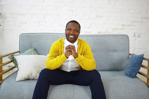 Przystojny, wesoły ciemnoskóry mężczyzna w dżinsach i żółtym swetrze, siedzący na wygodnej sofie w salonie, ściskający dłonie i uśmiechający się szeroko, pokazujący swoje białe idealne zęby