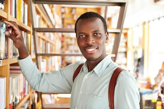 Przystojny wesoły hipster spędzając poranek w księgarni