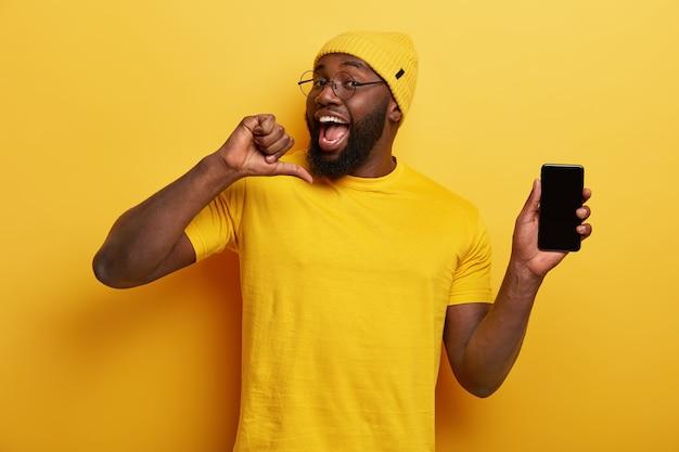 Przystojny, wesoły mężczyzna wskazuje na siebie, czuje się dumny z tworzenia nowej aplikacji, pokazuje ekran telefonu komórkowego