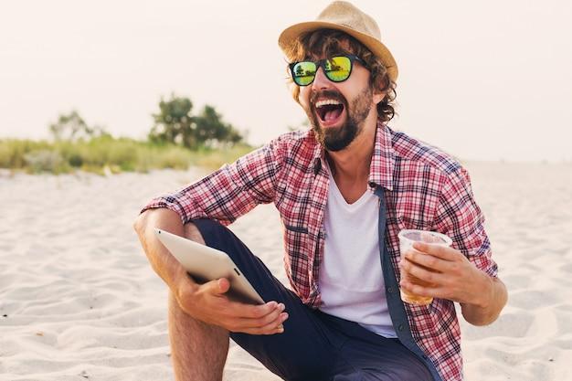 Przystojny wesoły mężczyzna z brodą w słomkowym kapeluszu, kraciastej koszuli i stylowych okularach przeciwsłonecznych siedzi na białym piasku i przy użyciu tabletu