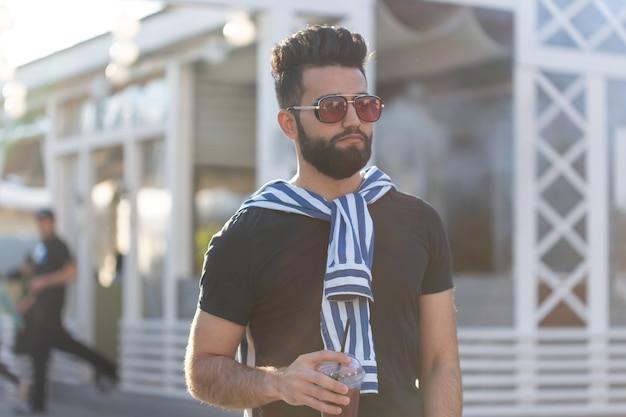 Przystojny wesoły młody arabski student ze stylowym wąsem i brodą z sokiem w dłoniach, spacerujący po mieście po całym dniu pracy. pojęcie pozytywu i odpoczynku.