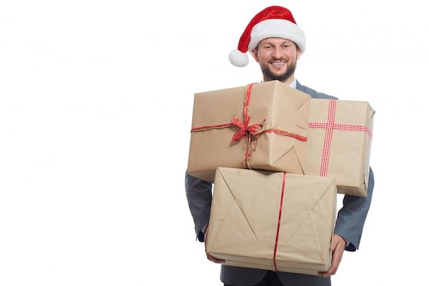 Przystojny wesoły młody biznesmen posiadający stos zapakowane prezenty świąteczne uśmiechnięty na białym tle