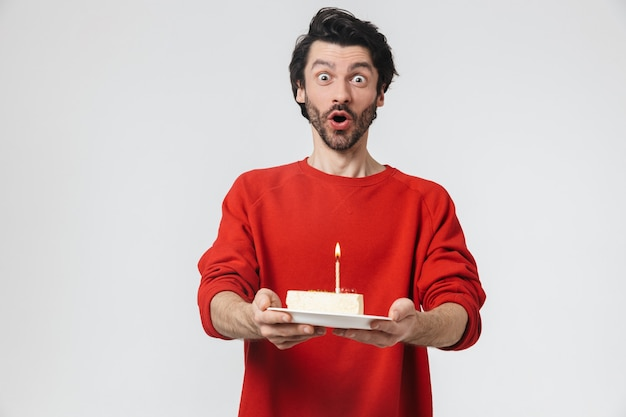 Przystojny, wesoły młody brodaty mężczyzna brunetka ubrany w sweter stojący nad białym, trzymając talerz z kawałkiem tortu urodzinowego ze świecą