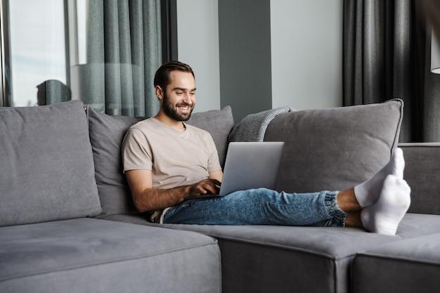 Przystojny wesoły młody człowiek pomieszczeniu w domu na kanapie przy użyciu komputera przenośnego.