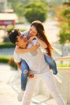 Przystojny, wesoły młody mężczyzna jeździ na barana swojej ładnej dziewczynie, gdy są na romantycznej randce