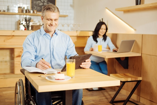 Przystojny wesoły niepełnosprawny mężczyzna siedzi na wózku inwalidzkim i pisze w swoim notatniku i pracuje na swoim tablecie w kawiarni i kobieta siedzi w tle