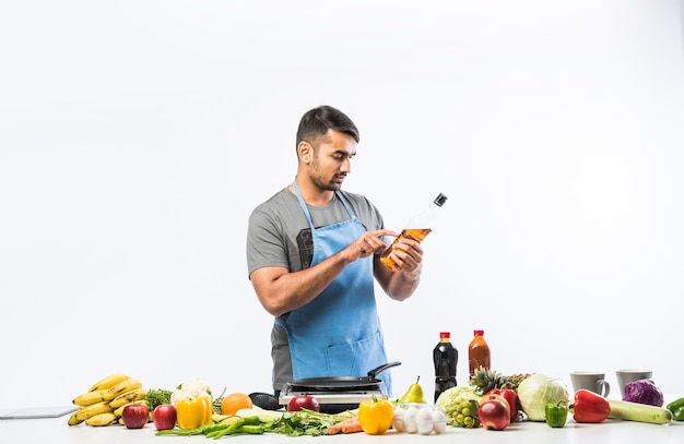 Przystojny wesoły uśmiechający się indianin przygotowuje posiłek w kuchni, zdrowa żywność, koncepcja gotowania.
